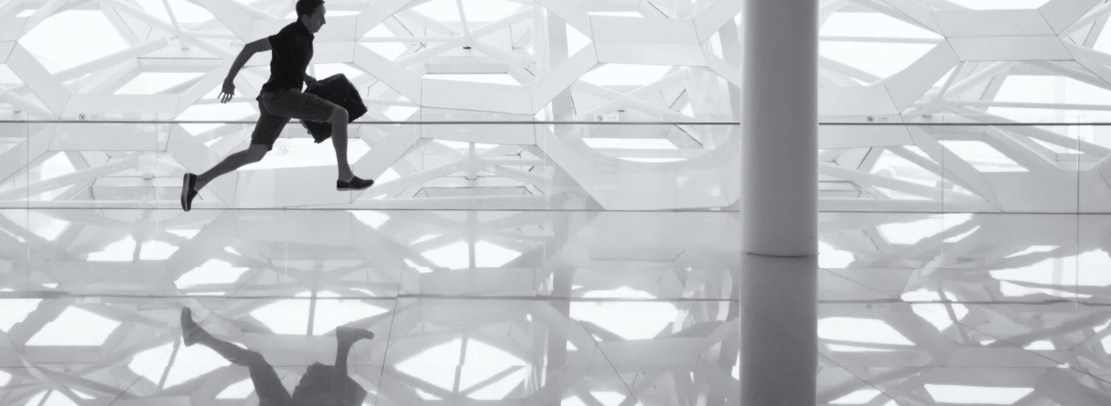 Photo en noir et blanc d'un homme courant de gauche à droite dans un décor géometrique aux nombreux reflets.