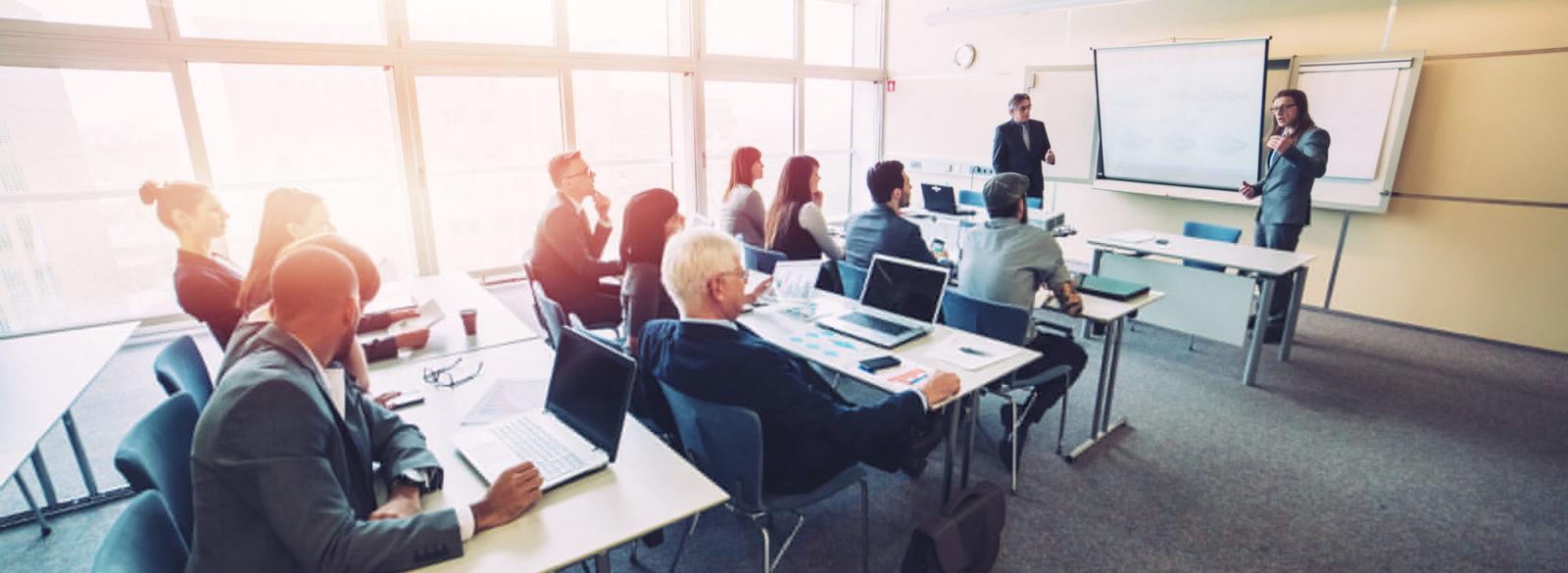 Deux hommes en costume font une présentation devant une salle de classe remplie d'hommes et de femmes d'affaire.